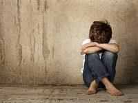 ילד יושב על הרצפה ומסתיר את עיניו עם ידיים על הבירכיים